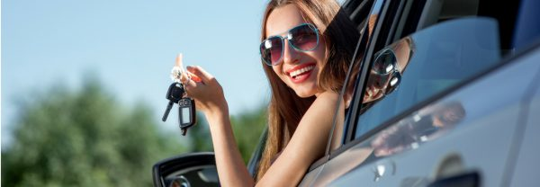 Woman in sunglasses dangling car keys out of window