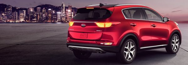A red 2019 Kia Sportage parked in front of a city skyline