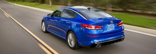 Blue 2019 Kia Optima driving down a country highway.