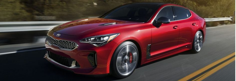 Red 2019 Kia Stinger driving along a highway.